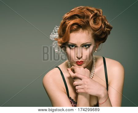 Beautiful retro young woman grimacing on gray background