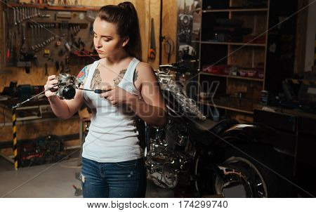 Well done. Attractive girl with long ponytail wearing casual clothes looking attentively at spare part while standing in the workshop
