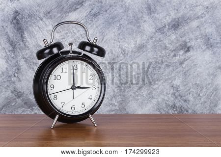 3 O'clock Vintage Clock On Wood Table And Wall Background