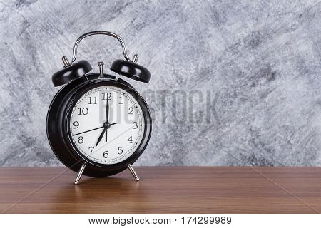 7 O'clock Vintage Clock On Wood Table And Wall Background