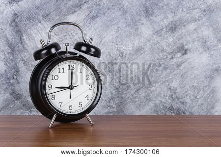 9 O'clock Vintage Clock On Wood Table And Wall Background