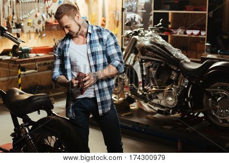 High spirit. Delighted man wearing jeans and blue checked shirt holding rag in both hands standing between two bikes