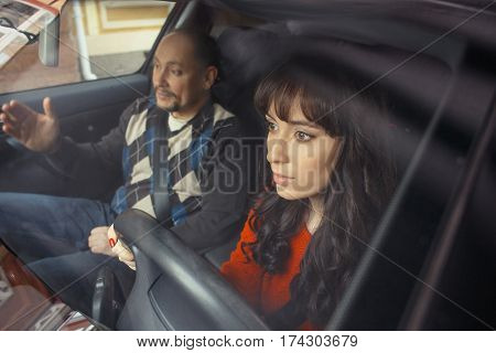 Male driver instructor and young woman seating in car