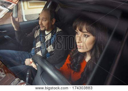 Male driving instructor arguing with frightened young woman holding steering wheel