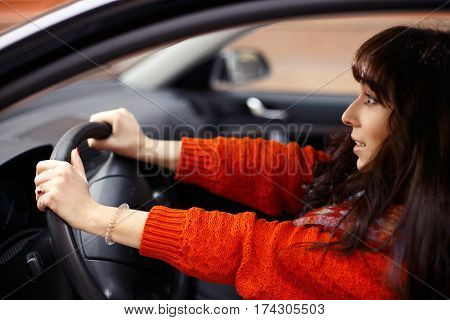 young woman in orange sweater looking frightened in front of the car