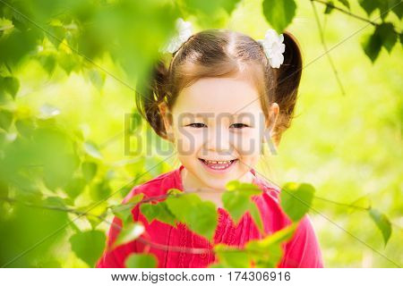 Closeup portrait of cute funny laughing girl of four years old playing cheerfully outside in spring sunny city park. Horizontal color photography