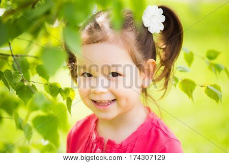 Closeup portrait of cute funny laughing girl of four years old playing cheerfully outside in spring sunny city park. Horizontal color photography.