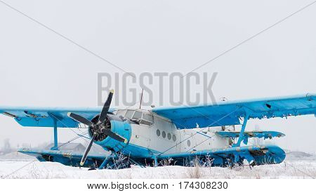 Old blue biplane on the ground in winter time
