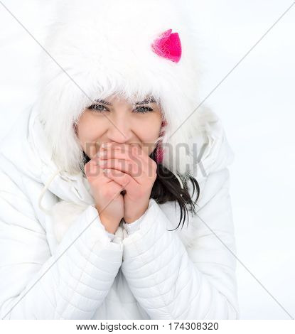 freezing young woman warming her hands in winter