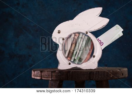 Rabbit Moneybox With Euro Banknotes And Coins On Dark Blue Background