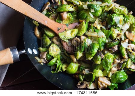 Delicious sauteed brussels sprouts with mushrooms in large skillet wood turner kitchen towel on table healthy dish top view close up
