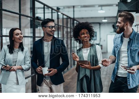 Friendly business chatter. Full length of young colleagues in smart casual wear discussing something while standing in office hallway
