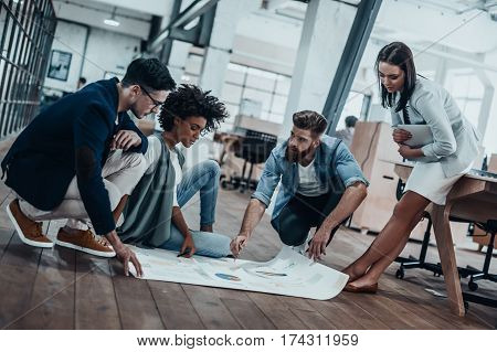 Going over details. Group of confident business people discussing something while looking at blueprint laying on the floor
