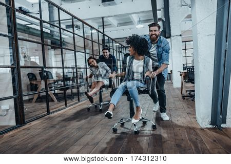 Team! Four young cheerful business people in smart casual wear having fun while racing on office chairs and smiling