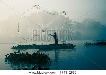 Fisherman casting out his fishing net in the river by throwing it high up into the air early in the blue colored morning to catch fish with his little fishing boat.