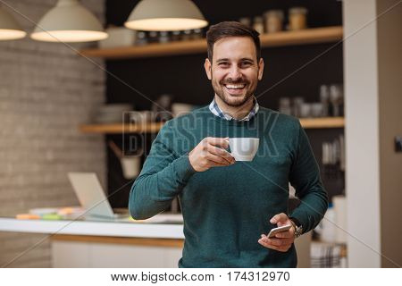 Handsome man drinking coffee at home in the kitchen.