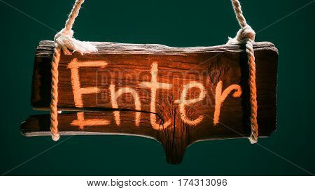 Wood signboard hanging on ropes over chroma key background. Text 'Enter' on the signboard