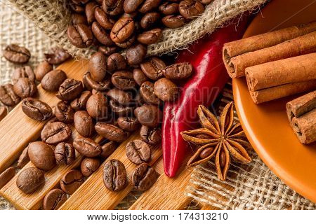 red chili pepper coffee beans cinnamon sticks and star anise on burlap background