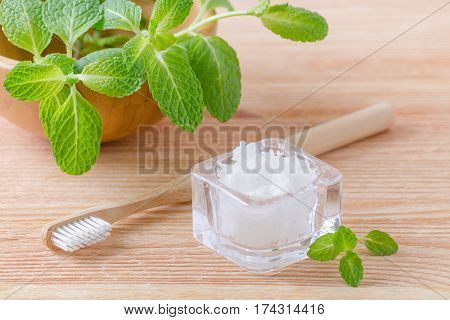 alternative natural toothpaste coconut oil and wood toothbrush closeup mint on wooden background