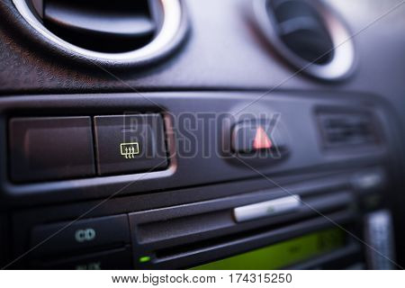 Defrost button detail on a car's dashboard.