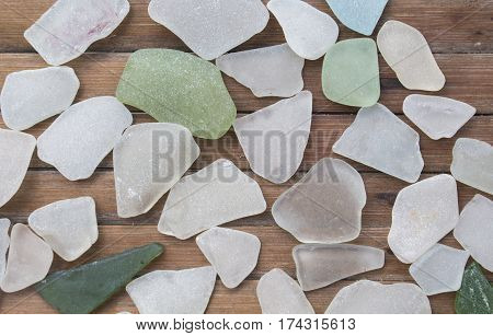 Smooth sea glass on wooden background. Beach glass collection with white and green glass pieces. Glass pebbles mosaic on timber board. Rustic and shabby seaside decor. Seashore finding photo wallpaper