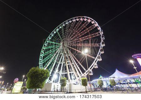 ABU DHABI UAE - NOV 26 2016: Marina Eye ferris wheel at the Marina Mall illuminated at night. Abu Dhabi United Arab Emirates