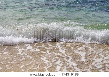 Curly sea wave with white foam splashing over beach. Clear turquoise blue sea water over white sand. Tropical island seaside. Seawater during high tide. Stormy seashore photo for banner or wallpaper