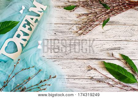 A bunch of pussy-willow branches on a white wooden background decorated with tiffany blue colored drapery. Springtime background.