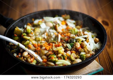 Brussels sprouts roasted with vegetables and beans in a frying pan
