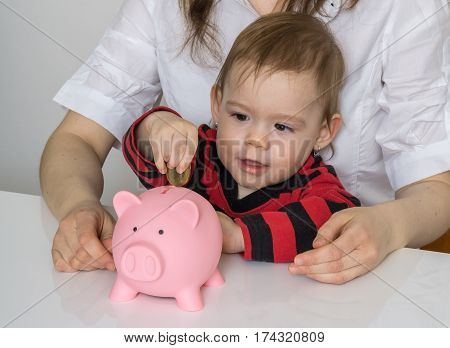 Savings For Future. Little Girl Is Putting Coins In Piggy Money