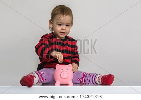 Little Girl Is Putting Coins In Piggy Money Bank. Savings And Ba
