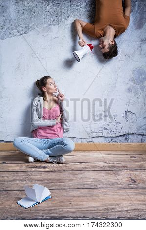 Woman Quieting Man With Megaphone