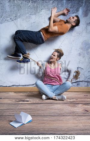 Violent woman holding rope tied around man's ankle controlling partner poster