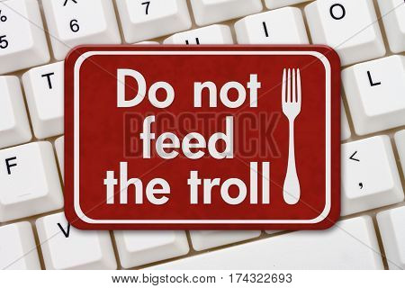 Feed troll sign A red sign with text Do not feed the troll and fork icon on a keyboard 3D Illustration