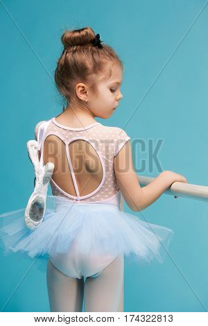 The little girl as balerina dancer standing with ballet shoes on blue studio background