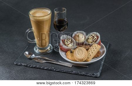 right side view on an aromatic coffee latte with three buttered muffins and petit fours on a white saucer liqueur in a glass spoon and forks the whole on a black stone plate sweet set