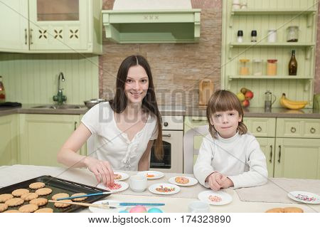 Young mum and her little son baking together and decorating the cupcakes.