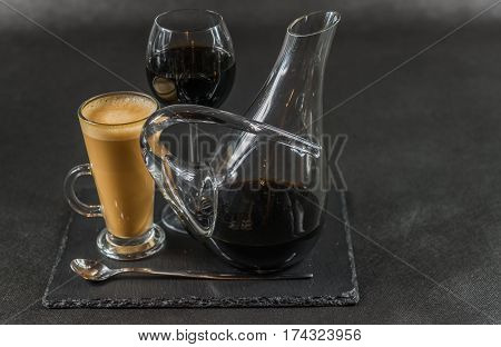 aromatic coffee latte with red wine in a carafe and glass teaspoon whole black stone plate drinks set