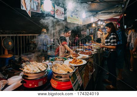 CHIANG MAI THAILAND - AUGUST 27: Thai woman sales at the Saturday Night Market on August 27 2016 in Chiang Mai Thailand.