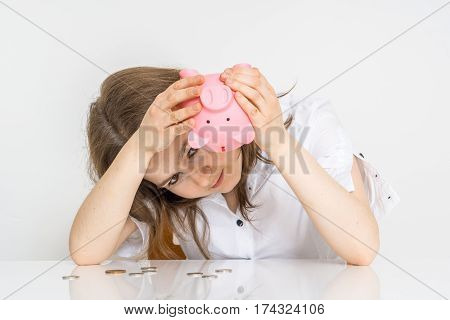Young Woman With No Money Is Looking In Empty Piggy Money Bank.