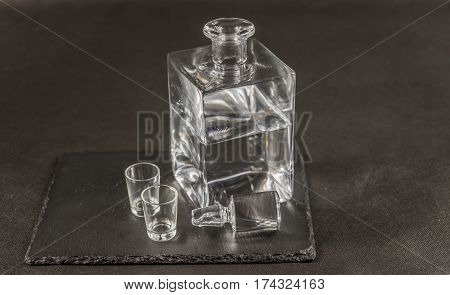 pure vodka in crystal modern carafe with a beautiful stopper and two glasses the whole on a black stone plate drinks set