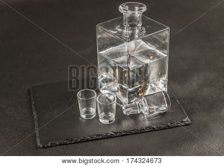 left side view on a pure vodka in crystal modern carafe with a beautiful stopper and two glasses the whole on a black stone plate drinks set