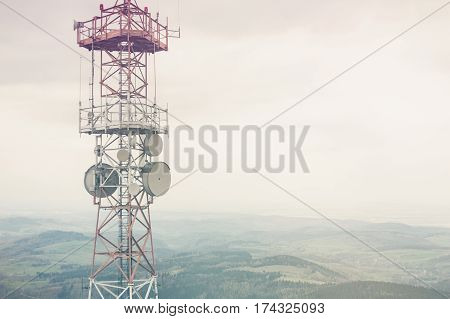 Radio mast over a cloudy valley background