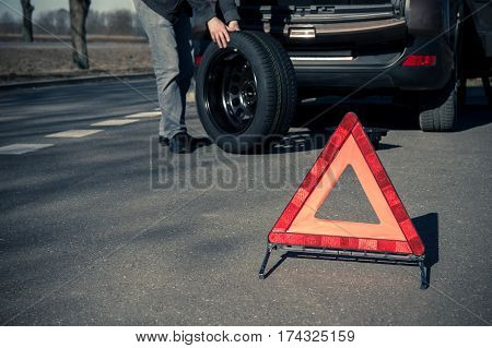 Warning triangle stands on the tarmac road and man holds the spare tire on the background