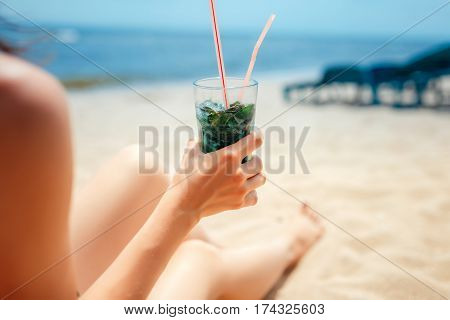 Woman holding glass of fresh mojito cocktail on the beach