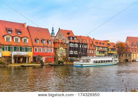 Bamberg city center view with river, half-timbered colorful houses on water and boat