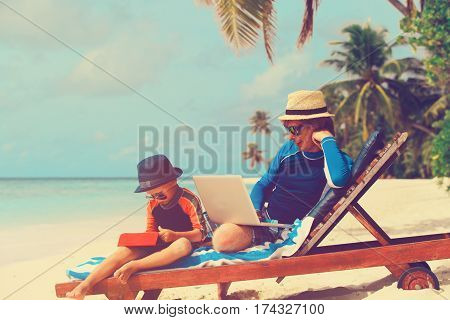 family with laptop and touch pad on tropical beach