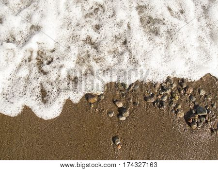 White foamy wave over sand beach. Clean tide during the day. Tropical beach top view photo. Relaxing view of seawater n sand. Exotic beach banner template or card background. Gold sand with pebbles