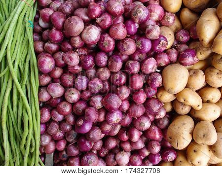 Potato onion and beans on shop's display. Long beans red onion and golden potato composition. Farm market in tropical country Philippines. Exotic vegetables on table for sell. Fresh ripe vegetables