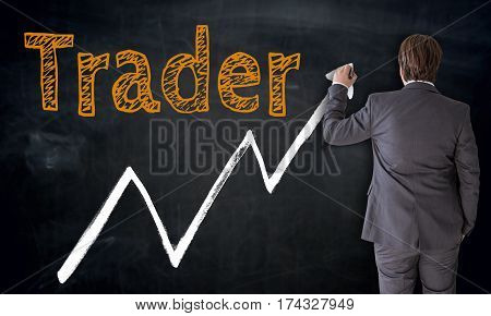 Businessman writing trader on blackboard concept picture